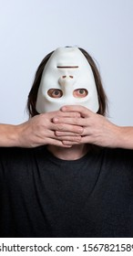 A long-haired man holds a white mask upside down near his face. Vertical frame. The concept of hiding a person, peeping, mental problems, a split personality, psychedelia or voodoo ritual.