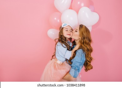 Long-haired mother and daughter in same denim shirts cute embrace at festive event with white balloons. Portrait of young beautiful woman kissing her child at birthday party on pink background