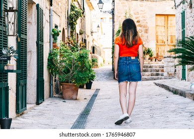 A Long-haired person exploring rural areas with red backpack and striped hipster shirt.