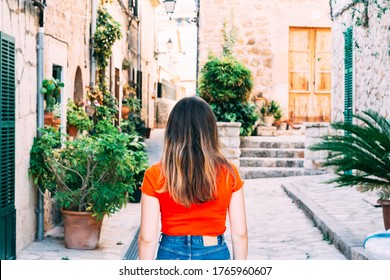 A Long-haired person exploring rural areas in Mallorca with red backpack and striped hipster shirt.