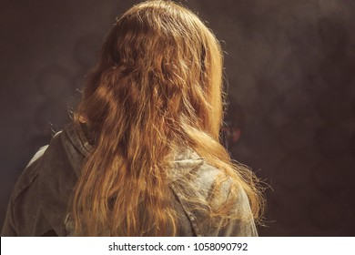 long-haired redheaded man standing with his back