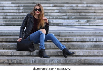 Long-haired skinny woman in black sunglasses sitting on stairs with bag. Legs bent at knees, arm near hair. Leather jacket, jeans, heels. Holes on jean trousers, urban fashion.