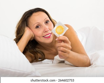 Long-haired smiling adult woman holding condom in bed