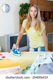 Long-haired smiling girl ironing with iron and ironing board at home