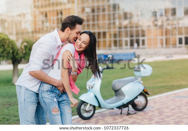 Long-haired smiling girl in ripped blue jeans having fun with boyfriend in city park. Outdoor portrait of funny loving couple fooling around on the street with scooter on background.