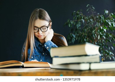 Longhaired student girl wearing glasses sitting by wooden table and preparing to the exams