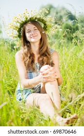 long-haired   teen girl  in camomiles chaplet in grass