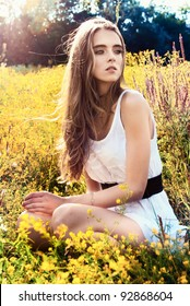 long-haired teen girl is sitting on flowers meadow
