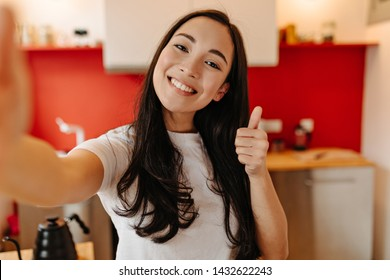 Long-haired woman dressed in white T-shirt makes selfie in kitchen and shows thumb up