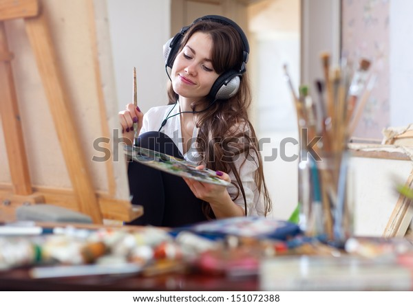 Long-haired woman in headphones  paints with oil colors and brushes on canvas in workshop interior