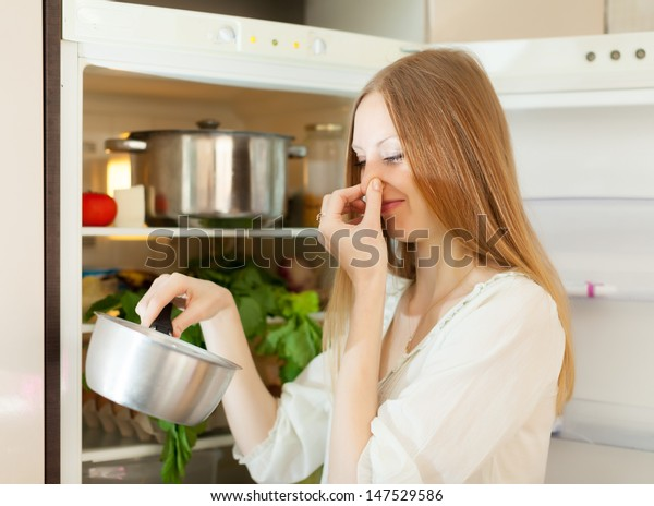 Long-haired  woman  holding her nose because of bad smell near fridge at home