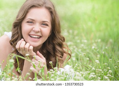 Long-haired woman resting in a clearing with flowers. Rest in the village. Lifestyle photography. Skin and hair care