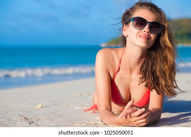 longhaired woman in sunglasses and swimsuit at beach. Praslin, Seycheles