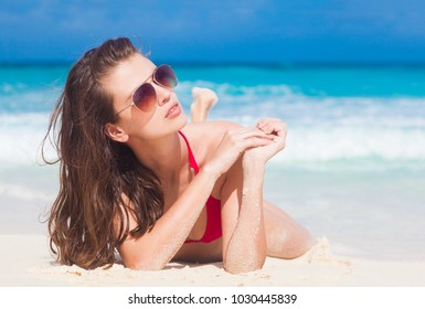 longhaired woman in sunglasses and swimsuit at beach. La Digue, Seychelles