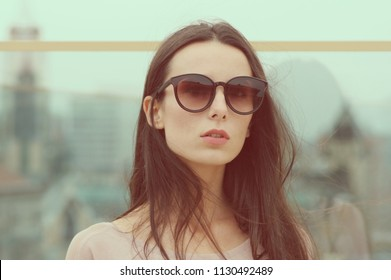 Long-haired young brunette woman posing in the city against a glass wall in big sunglasses. Fashionable style with pink tones. Blurred background.