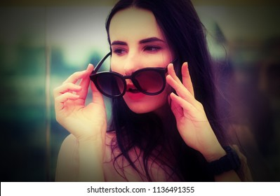 A long-haired young brunette woman posing while playing with sunglasses. Fashionable style with pink tones. Blurred background. The wind plays with brunette hair.