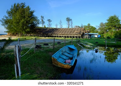 Longhouse with boat on lakeside, borneo, kudat sabah malaysia. image has grain or blurry or noise and soft focus when view at full resolution.  (Shallow DOF, slight motion blur)