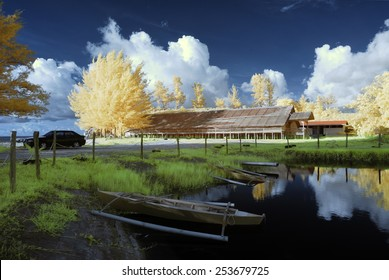 longhouse with boat on lakeside in infrared, borneo, kudat sabah malaysia Image has grain or blurry or noise and soft focus when view at full resolution.  (Shallow DOF, slight motion blur)