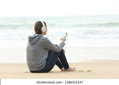 Longing teen alone listening to music sitting on the sand on the beach