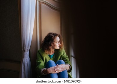Longing woman meditating and looking through the window. Warm dressed caucasian girl with curly hair.