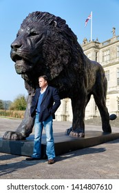 Longleat House, Wiltshire / UK- March 17 2016: African based sculptor Bruce Little stands next to his monumental lion sculpture which was commissioned by Ceawlin Thynn, Viscount Weymouth of Longleat