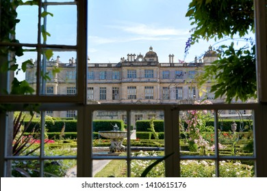 Longleat, Wiltshire / UK - July 17 2014: A view of Longleat House in Wiltshire looking out through the windows of the Orangery across the rose-filled Love Labyrinth Garden.