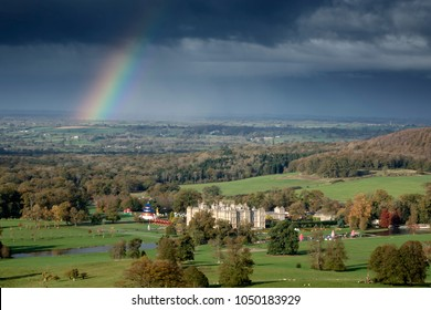Longleat, Wiltshire, UK - November 4, 2014: A rainbow and dark storm clouds contrast with the autumnal sunshine and seasonal colours over Longleat House in Wiltshire UK.