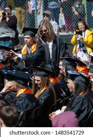 """Longmont, Colorado / USA - May 25 2019:  Boy with Autism and Down's Syndrome gives his classmate a """"high five"""" during the graduation ceremony at Mead High School, a Unified Champion School."""