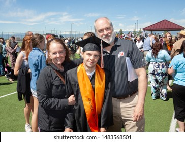 Longmont, Colorado / USA - May 25 2019: A young man with autism and Down's Syndrome poses with his parents after graduating from Mead High School, a Unified Champion School which promotes inclusion.