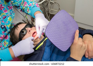 Longmont, Colorado, USA - May 9th, 2017:  Teenage boy with Autism and Down's Syndrome holds a mirror as he is taught proper dental hygiene and flossing