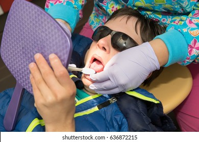 Longmont, Colorado, USA - May 9th, 2017:  Teenage boy with Autism and Down's Syndrome holds a mirror as he is taught proper dental hygiene and brushing