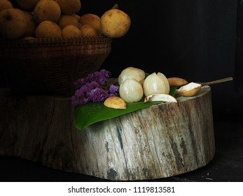 longong in still life,Thai fruits Peeling Placed on the old wooden cutting board in dim light,backdrop has a lot of wollongong that are not peeled.In black background, There is space for text input.