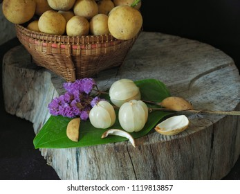 longong Thai fruits in brown rattan baskets placed on old wooden boards. In still life the beautiful on black background. There is space for text input, About Thai fruits in southern Thailand.