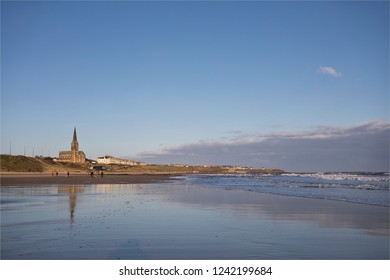 The Longsands at Tynemouth on the North East Coast of England on a cold, windy November morning with the blue sky reflecting on the wet sand.