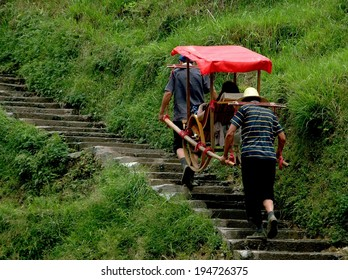 Longsheng, China - May 2, 2006:  Porters carry a tourist seated in a covered sedan chair up a steep flight of stone stairs to the ancient Yao village of Ping-An in China's Guang Xi Province