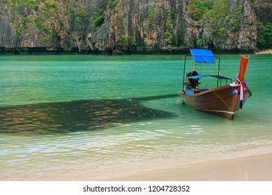 Longtail boat anchored at Maya Bay next to school of fish on Phi Phi Leh Island, Krabi Province, Thailand. It is part of Mu Ko Phi Phi National Park.