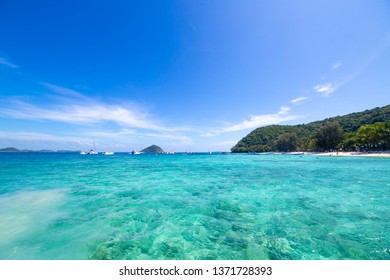 Longtail boat with turquoise water and white sand under blue sky at Coral Island Thailand