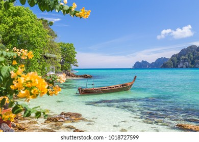 Long-tail boats, the Andaman Sea and hills in Ko Phi Phi Don, South Thailand. Clear blue water can be seen.