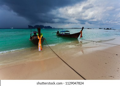 Longtail boats near the beach under dramatic gloomy sky. Phi Phi. Thailand