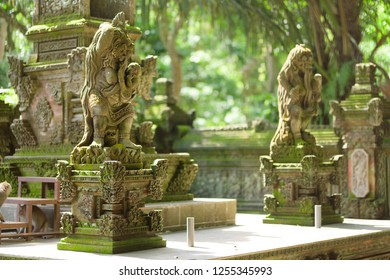 Long-tailed macaque monkeys roam free amongst the balinese Hindu temples of the sacred Ubud Forest in Bali, Indonesia.