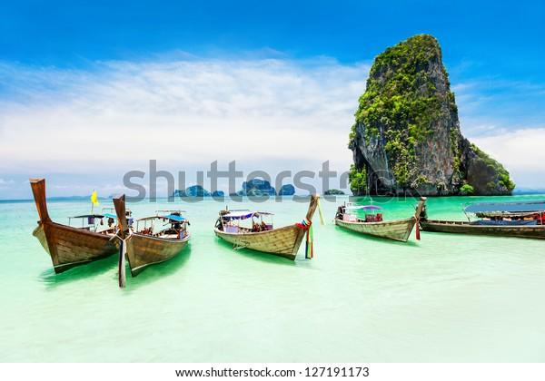 Langboote am Phuket Strand mit Kalkstein auf thailändischem Hintergrund. Die Insel Phuket ist ein beliebtes Reiseziel in Thailand.