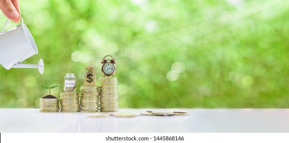 Long-tern investment, time value of money concept : Clock, US dollar bag, glass jar, a small tree on steps of rising coins. Hand pour water from a watering can, depicts asset growth from investment
