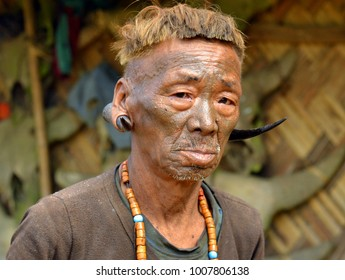 LONGWA, NAGALAND, INDIA - NOV 1, 2017: Three-quarter head shot of an old Konyak Naga warrior and ex-headhunter with facial tattoo, tribal hairstyle, and deer horns in his earlobes, on Nov 1, 2017.