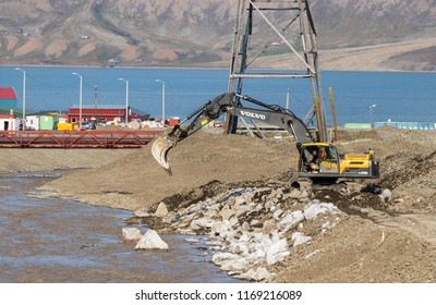 Longyearbyen, Svalbard, Norway - August 13th, 2018: A man driving a Volvo excavator working next to the port.