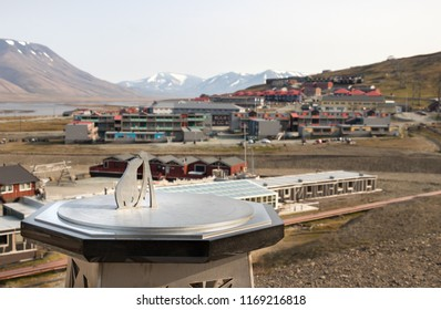 Longyearbyen, Svalbard, Norway - August 13th, 2018: The Longyearbyen Sundial made by Lindisfarne in England and the city center in the background.