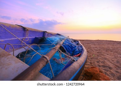 a lonley boat by the beach at dawn