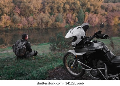Lonley concept, man is sitting alone and look at the distance. Adventure motorcycle, Motorcyclist, A motorbike driver looks, concept of active lifestyle, enduro travel road trip, destination