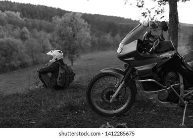 Lonley concept, man is sitting alone and look at the distance. Adventure motorcycle, Motorcyclist, A motorbike driver looks, active lifestyle, enduro travel road trip, destination, black and white