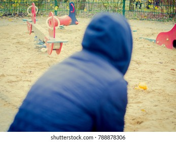 Lonley man looking at a playground