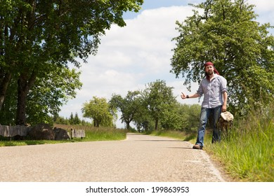 lonley man on a road holding thumb up